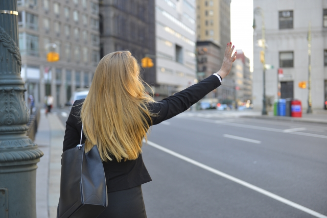 タクシーを止める女性